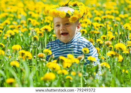 Little baby in flowers chaplet at meadow - stock photo