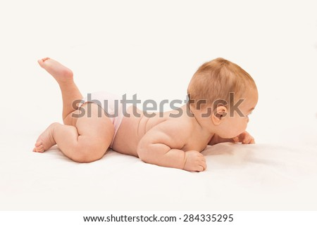 Little baby in pants lying on his tummy with his head up, trying and learning to crawl on light sheet background. Side view.