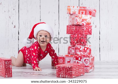Little baby in red with cap crawling and smiling next to gift tower - stock photo
