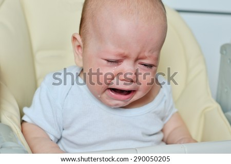 little baby is crying and sitting on the chair - stock photo