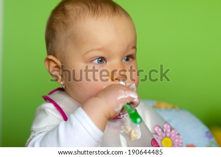 little baby is eating alone - stock photo