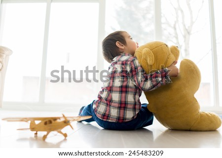 Little baby kid sitting in living room with toy bear - stock photo