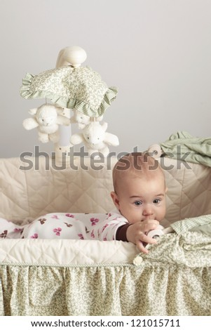 Little baby kneel in the crib and trying to get out - stock photo