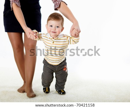 little baby learning how to walk with a parent