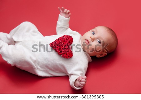 little baby lying down on red background with heart shape toy as a gift for Valentine's Day  - stock photo