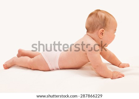 Little baby lying on his tummy with his head up, trying and learning to crawl on light sheet background. Side view. - stock photo