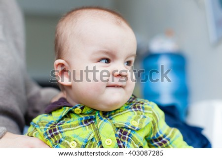 Little baby makes faces at the background of water cooler, closeup portrait, smiling, nice - stock photo