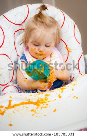 Little baby making a mess with her food - stock photo