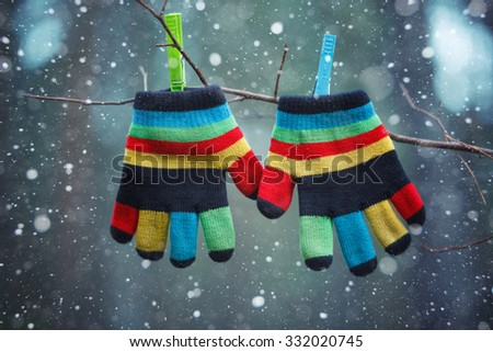 Little baby mittens/gloves hanging by a thread in winter day under the falling snow. Winter symbol - stock photo