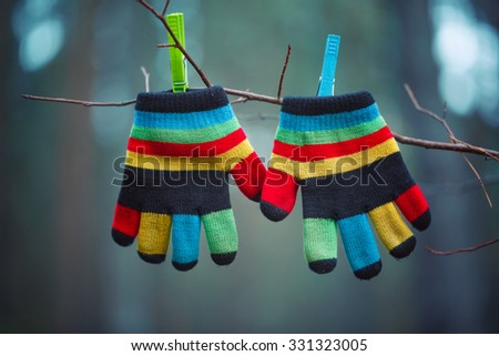 Little baby mittens/gloves hanging by a thread in winter outside - stock photo
