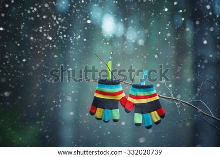 Little baby mittens/gloves hanging by a thread in winter outside. - stock photo