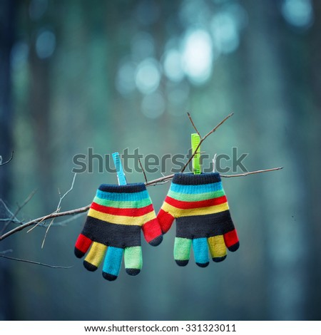 Little baby mittens/gloves hanging by a thread in winter outside. Winter symbol. - stock photo
