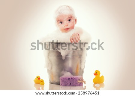 Little baby on a bucket on white background - stock photo