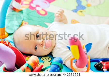 little baby on the carpet with toys - stock photo