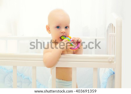 Little baby playing on the bed at home with toy - stock photo