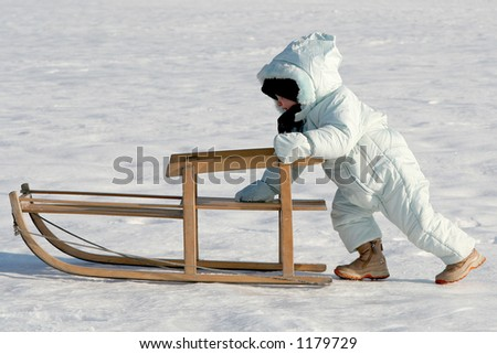 Little baby pushing her sled - stock photo