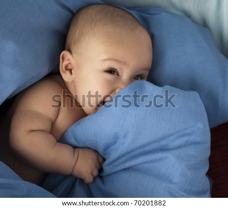 little baby resting under a blue blanket - stock photo
