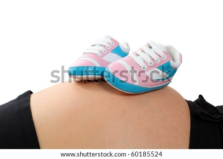 Little baby shoes on pregnant belly - stock photo