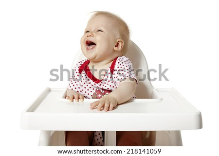 Little baby sitting at the table and shouting. Isolated on white background.  - stock photo