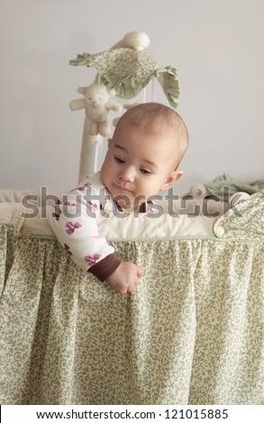 Little baby sitting in crib - stock photo