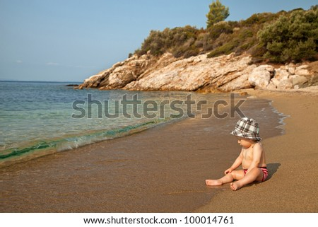 Little baby sitting on the beach and enjoying sea waves - stock photo