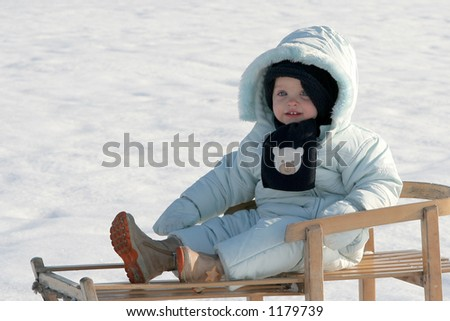 Little baby sitting on the sled - stock photo