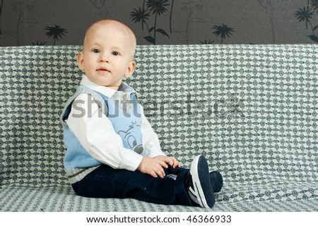 little baby sitting on the sofa - stock photo