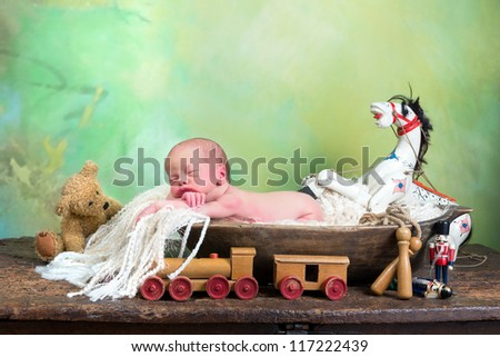 Little baby sleeping in a dough bowl surrounded by antique toys - stock photo