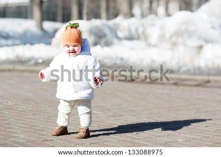Little baby taking her first steps on a sunny spring day - stock photo