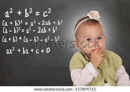 Little baby thinking about mathematics problem  - stock photo