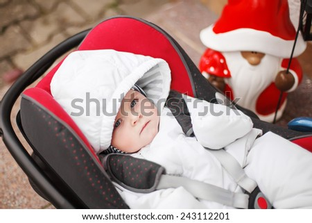 Little baby toddler in white winter clothes sitting in car seat. On cold winter day. Children safety in car concept. - stock photo