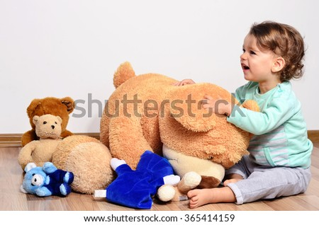 Little baby toddler playing and laughing with his teddy bears. Cute boy and his many big teddy bear toys. - stock photo