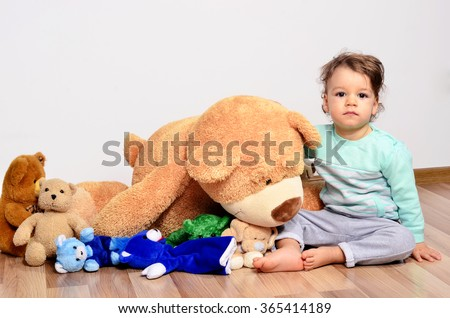 Little baby toddler playing with his teddy bears. Cute boy and his many teddy bear toys.