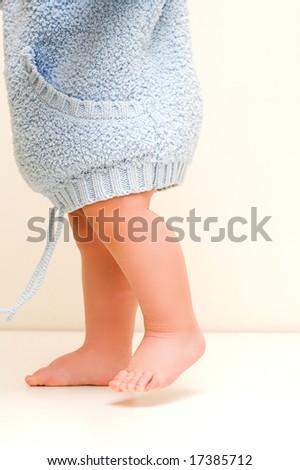 little baby walking in blue bathrobe - stock photo