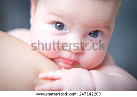 little baby watching over a shoulder - stock photo