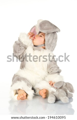 Little baby wearing bunny costume and playing with plushie on white background.