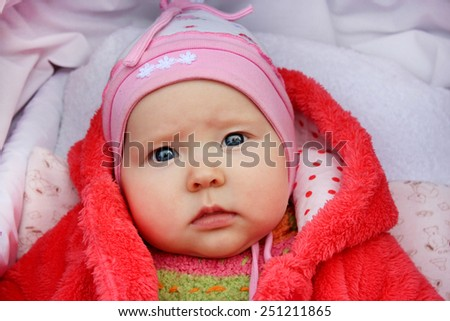 little baby with beautiful sad eyes in the perambulator