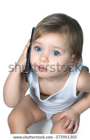 Little baby with blue eyes in a t-shirt sitting on the floor and talking on a large smartphone isolated on white background - stock photo