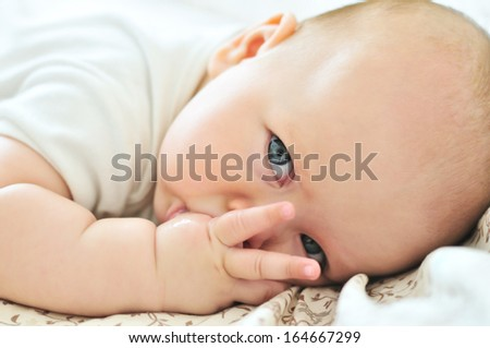 little baby with finger in mouth - stock photo
