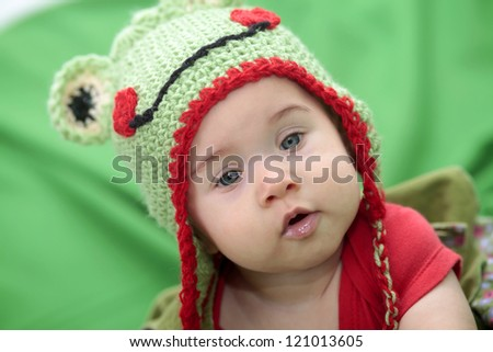 Little baby with frog hand knit hat - stock photo