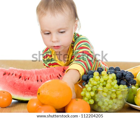 little baby with fruits, close up,  concept of health care and healthy child nutrition - stock photo
