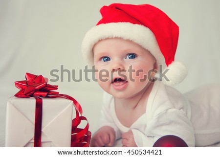 little baby with santas hat and a gift  - stock photo