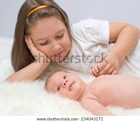 Little baby with sister on bed - stock photo