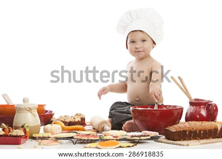 Little Baker.  Adorable little boy wearing a chef's hat and surrounded by baked goods.  Isolated on white with room for your text. - stock photo