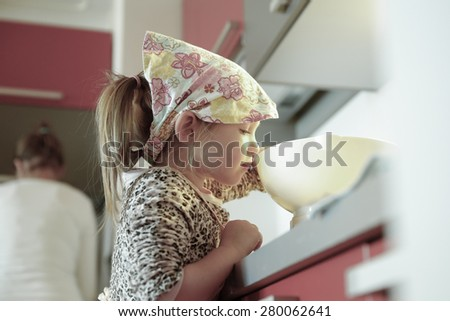 Little baker girl weighing flour for a birthday cake, being independent, helping mum in the kitchen. Independence, family values, inclusion, learning through experience concept.  - stock photo