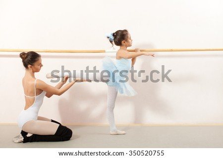Little ballerina dancing with personal ballet teacher in dance studio. Teacher helping little ballerina and they using stick on the wall - stock photo
