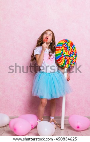 little ballerina eat lollipop and hold huge toy lollipop - stock photo