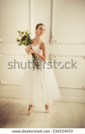 Little ballerina girl in a dress, classical, ballet dance. A girl in a ball gown sitting on sofa classic, white background, white sofa classic. - stock photo