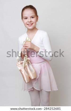 little ballerina holding ballerina shoes (pointe) - stock photo