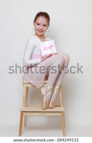 Little ballerina holding present box - stock photo